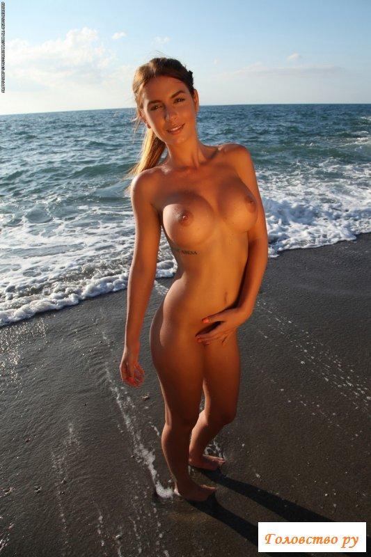 Обнаженная пляжница поливается из ведерка