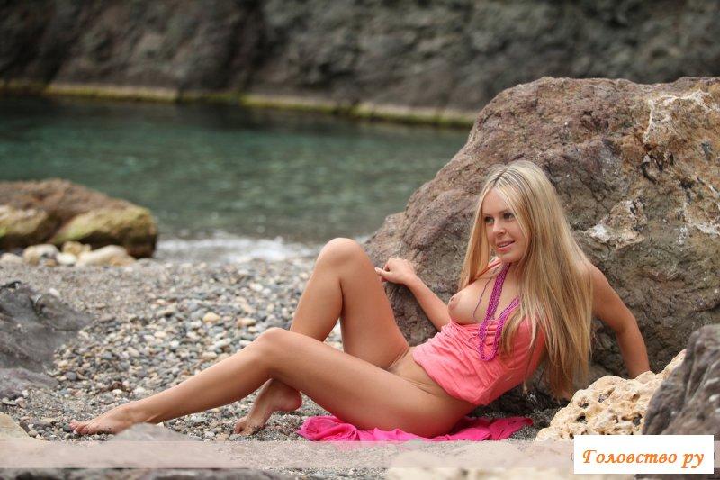 Обнажённая блондинка откровенно позирует на берегу моря