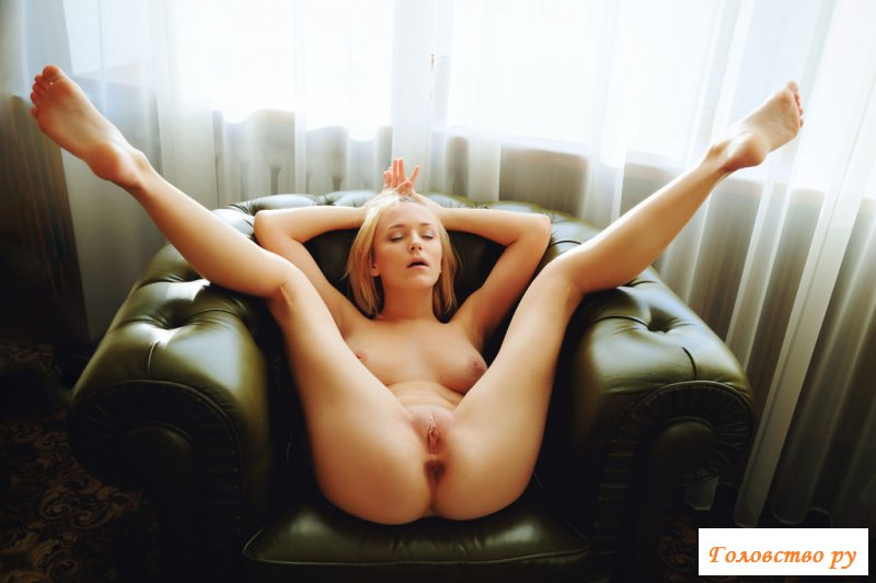 Голая блондинка красиво нежится в комфортном кресле