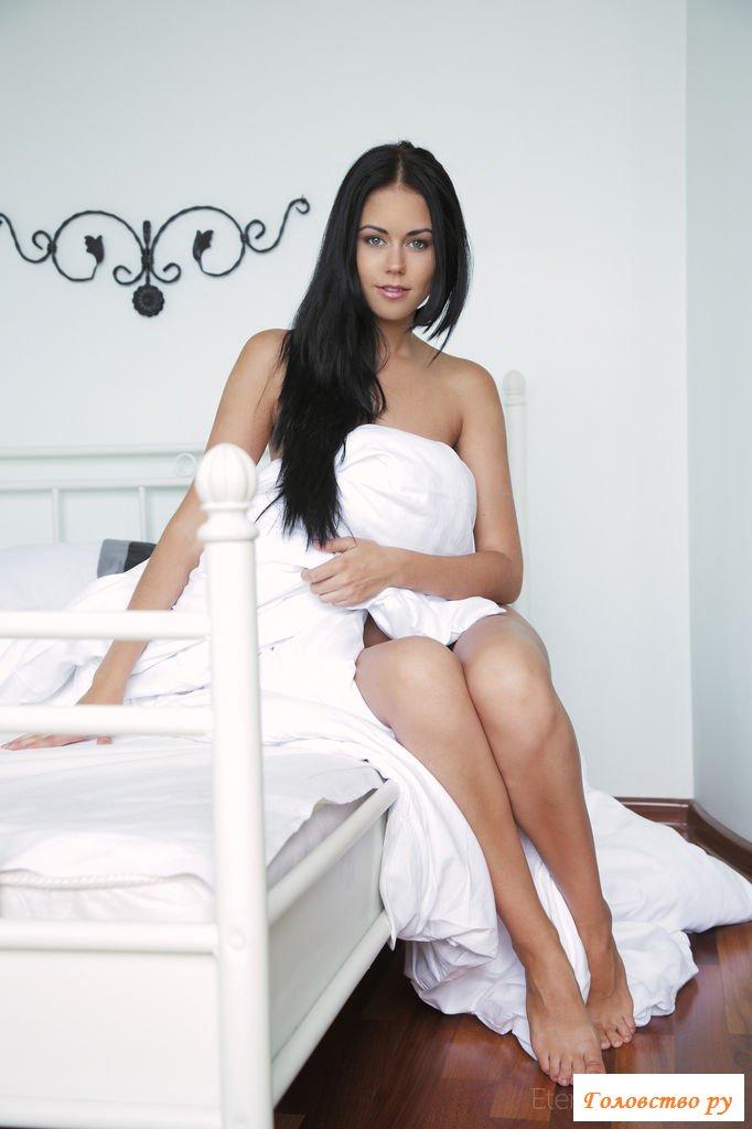 Нежная обнаженная брюнетка на белой постели